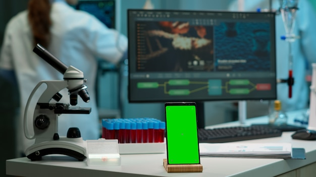 Geef telefoon weer met groen scherm, mock-up op sjabloon geplaatst op bureau in wetenschappelijk laboratorium terwijl team van medisch onderzoeker wetenschappers virusevolutie analyseren op digitale monitor die experiment uitvoert