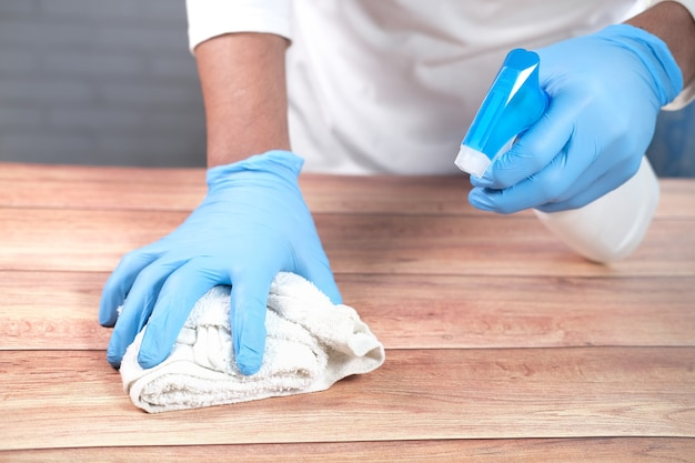 Geef wegwerphandschoenen met een desinfecterende spray om het tafeloppervlak schoon te maken