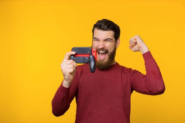 Geeft !!!! bebaarde man speelde online games en won, opgewonden feest met opgeheven arm en schreeuwend