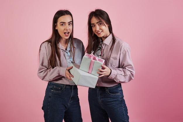 Geeft je kerstcadeautjes. jonge vrouwen die pret hebben. schattige tweeling