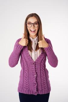 Geek jonge vrouw met omhoog geïsoleerde duimen