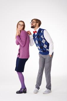 Geekman die verlegen geïsoleerde vrouw probeert te trekken