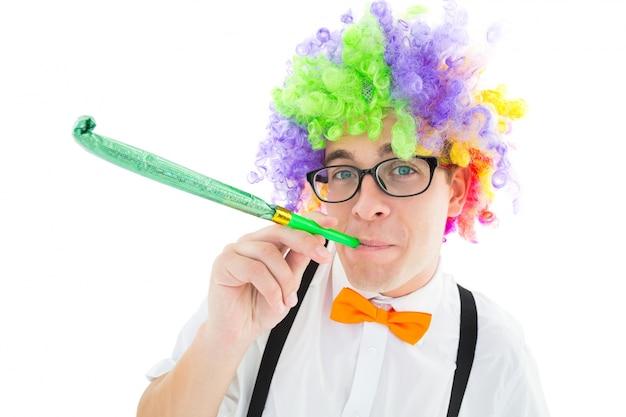 Geeky hipster die een hoorn van de regenboogpruik blazende partij draagt