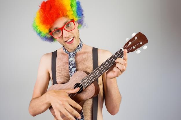 Geeky hipster in afro regenboogpruik het spelen gitaar