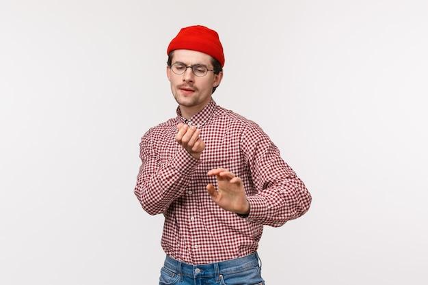 Geeky man vibing en plezier maken. zorgeloos leuke grappige man in rode muts en bril, onhandig dansend op de dansvloer, geniet van een geweldig kantoorfeest, viert vakantie of zegeviert over de overwinning