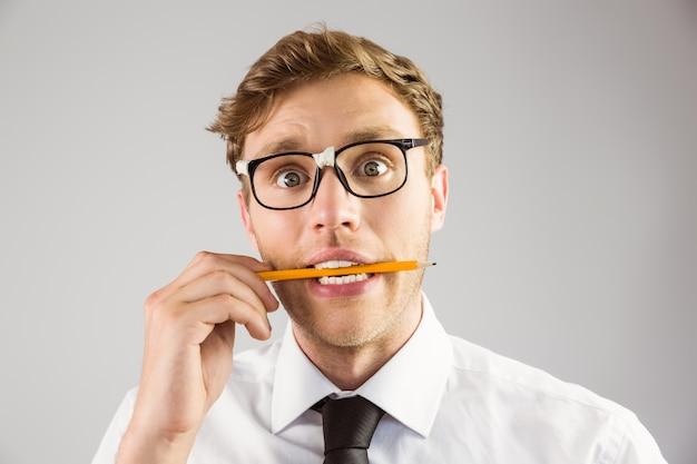 Geeky zakenman die een potlood bijt