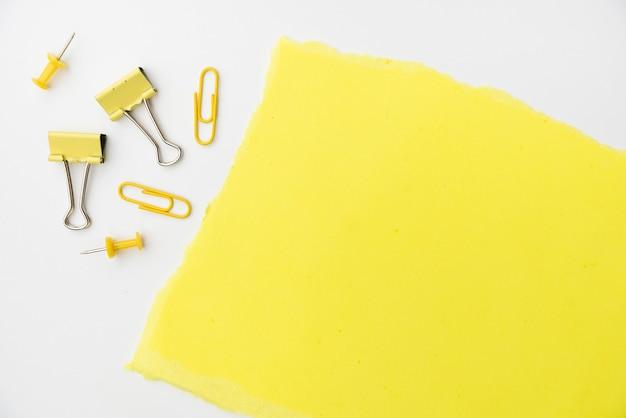Geel ambachtdocument met paperclip en punaise op witte achtergrond