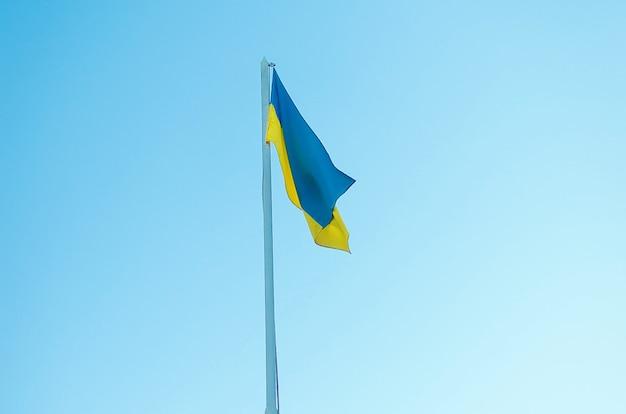 Geel-blauwe vlag van oekraïne op een paal tegen de blauwe lucht. de officiële vlag van de oekraïense staat