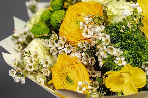 Geel boeket van gele en oranje bloemen op een grijze grijze achtergrond