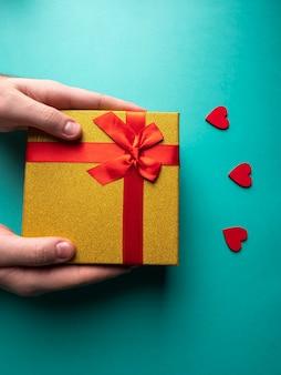 Geel cadeau met een rood lint vlinders knoop die in de handen is, en in de buurt van 3 rode harten op groen