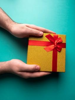 Geel cadeau met een vlinderknoop van een rood lint die in de handen op groen is