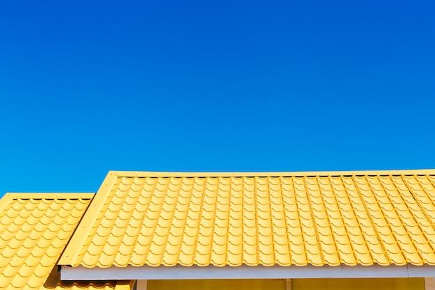 Geel dak met blauwe hemelachtergrond