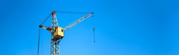 Geel de kraanclose-up van de bouwlift tegen de blauwe hemel, panoramische mock-up met ruimte voor tekst Premium Foto
