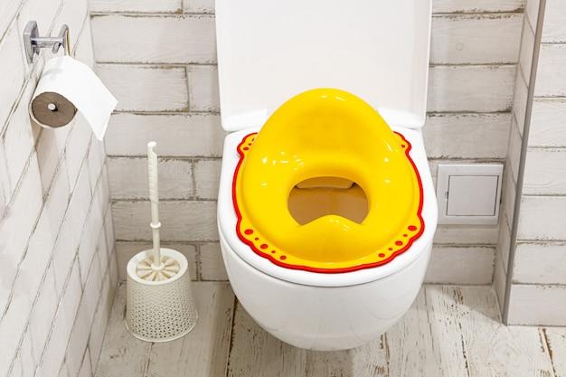 Geel deksel voor wc-bril voor kinderen hoe een kind aan het toilet te laten wennen witte badkamer