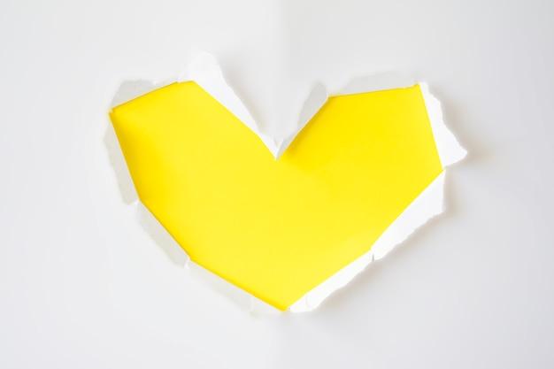 Geel document gat met gescheurde kanten in vorm van hart op witte achtergrond voor exemplaarruimte. wenskaart voor valentijnsdag, vrouwendag of bruiloft uitnodiging.