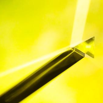 Geel driehoekig kristal met schaduw op gele achtergrond