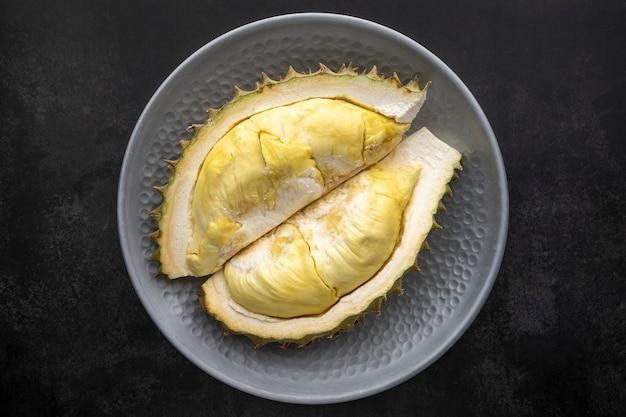 Geel durian monthong-vlees in metalen plaat op donkere textuurachtergrond, koning van fruit