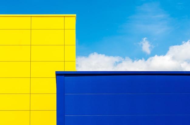 Geel en een blauw gebouw onder een blauwe lucht en zonlicht overdag