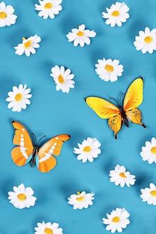 Geel en oranje vlinders en madeliefjes op blauwe achtergrond. bovenaanzicht. zomer achtergrond.