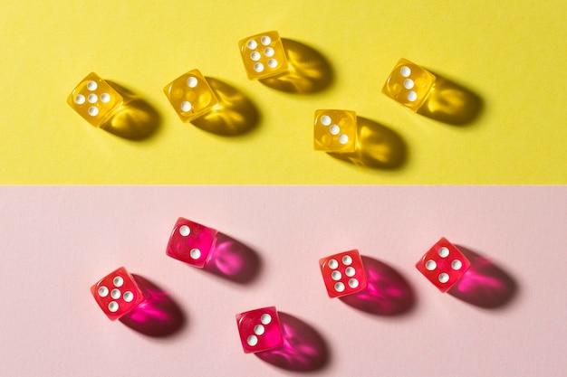 Geel en roze dobbelstenen op kleurrijke achtergrond