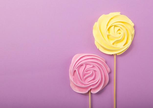 Geel en roze rose snoep in pastelkleuren op een houten stok op een grijze achtergrond, valentijn, moederdag.