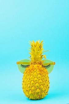 Geel geschilderde ananas in zonnebril met kunstmatige wimpers. humor, zomer patry concept