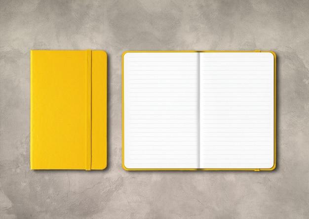 Geel gesloten en open bekleed notitieboekjemodel dat op concrete achtergrond wordt geïsoleerd