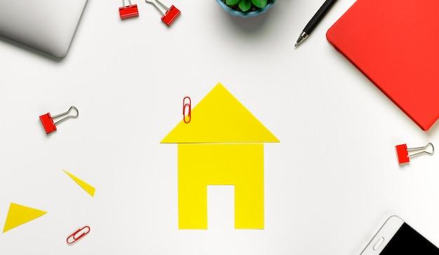 Geel gesneden huis met kantoorbenodigdheden