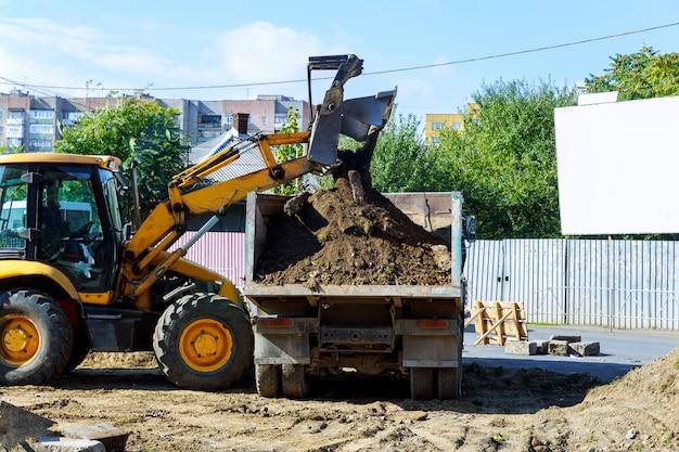 Geel graafwerktuig bij sandpit tijdens grondverzetwerken