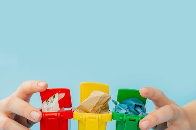 Geel, groen en rood prullenbakken met recycle symbool op blauw oppervlak. houd de stad netjes, laat het recyclingsymbool achter. natuurbescherming concept