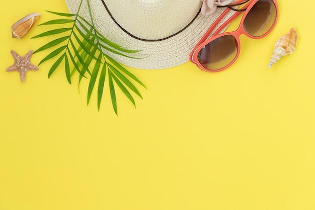 Geel helder zomeroppervlak met hoed, zonnebril, schelpen, zeesterren en bladeren