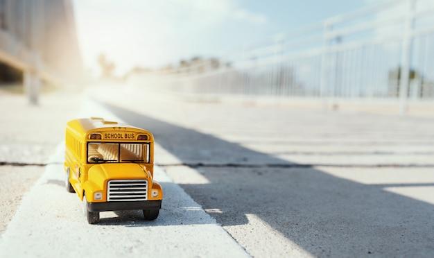 Geel het stuk speelgoed van de schoolbus model bij de landweg terug naar de achtergrond van het schoolconcept.