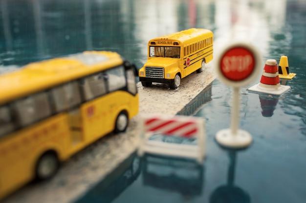 Geel het stuk speelgoed van de schoolbus model op de weg met verkeersteken, de regenachtige dag.