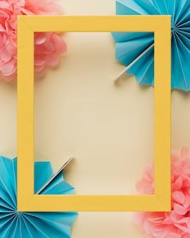 Geel houten grensfotoframe op document bloem over beige achtergrond