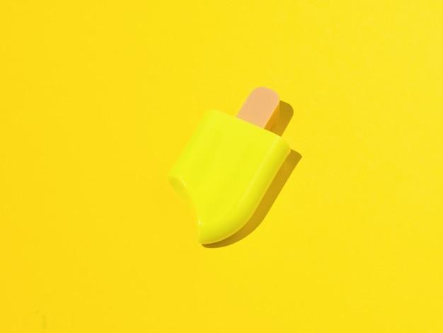 Geel ijs op een stokje op een gele achtergrond. een populaire zomersnack.