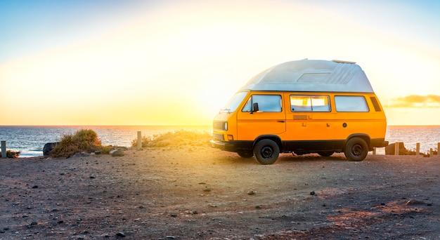 Geel kampeerbusje, staande op de klif bij zonsondergang