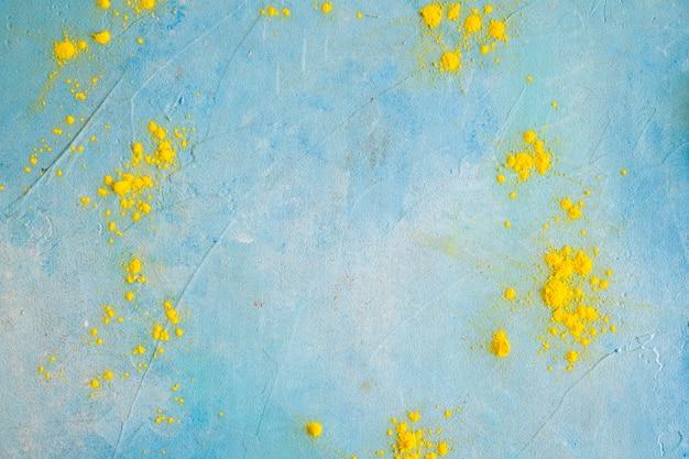 Geel kleurenpoeder op geschilderde blauwe muur