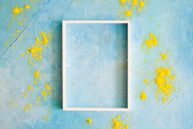 Geel kleurenpoeder rond het witte grenskader op geschilderde muur