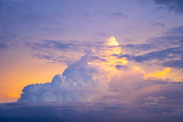 Geel licht van zonsondergang achter grote wolk op schemerhemel, mooie dramatische bewolkte hemel zoals hemel