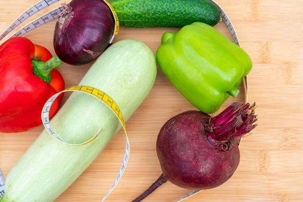Geel meetlint en groenten op een houten snijplank. gezonde levensstijl dieet.