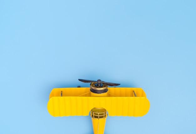 Geel metaalvliegtuig op blauwe exemplaarruimte op de bovenkant voor reisconcept