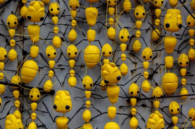 Geel mierenstandbeeld op de betonnen muur.
