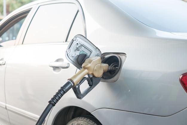Geel mondstuk tanken in de tank bij het benzinestation