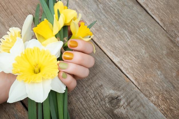 Geel nagelontwerp. vrouwelijke hand met glitter manicure met narcissus bloemen.