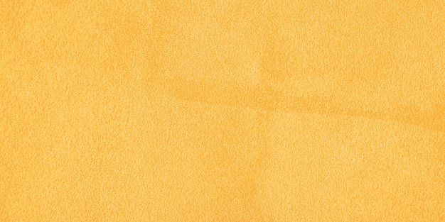 Geel natuurlijk suède als achtergrond met een donkere rand en een licht midden. horizontale webbanner.