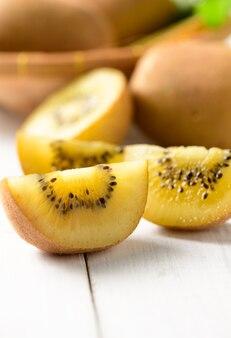 Geel of goud gesneden kiwi fruit op witte houten achtergrond, gezonde vruchten