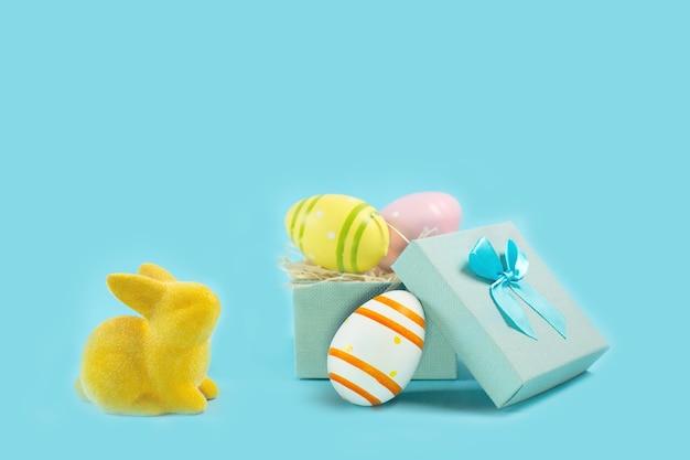 Geel paashaaskonijn met geschilderd ei in giftdoos op blauw bureau