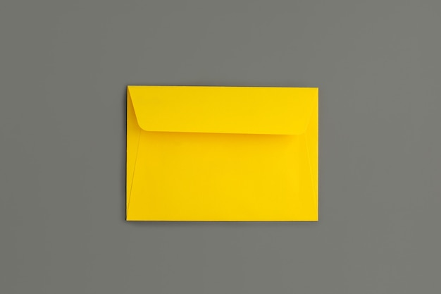 Geel papier envelop op grijs papier achtergrond. bovenaanzicht.