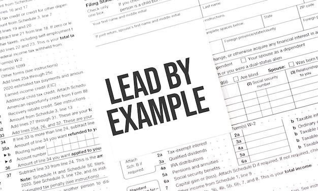 Geel papier opmerking met woorden leiden door het voorbeeld, belasting concept