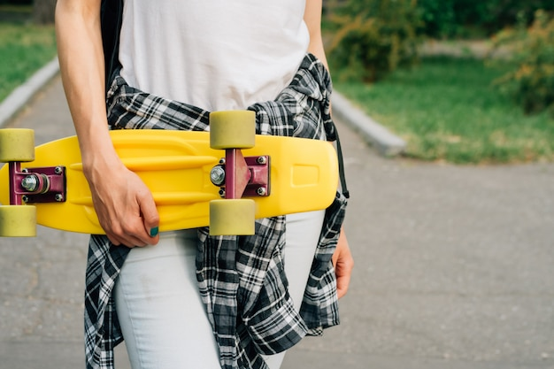 Geel plastic skateboard met groene wielen in vrouwelijke handen in openlucht in een park